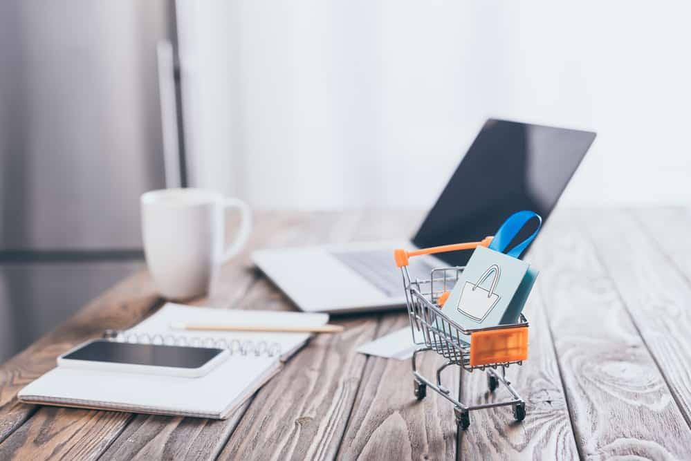 Laptop mit kleinem Einkaufswagen- visualisiert das online-Shopping